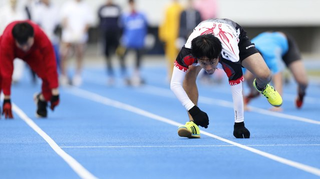 Takashi Kokubu, a 37-year-old actor, runs during a four-legged 100-metre race organized by Kenichi Ito (not pictured) in Tokyo November 14, 2013. (Photo by Yuya Shino/Reuters)