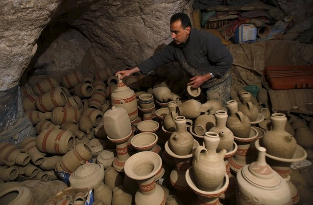 Palestinian Jamal Fakhori arranges clay jars and pots that he made in his pottery workshop in the West Bank village of Jabaa near Jenin January 31, 2016. (Photo by Abed Omar Qusini/Reuters)