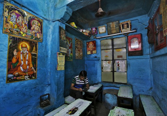 A man uses a mobile phone while sitting inside a tea shop with posters of Hindu deities pasted on the walls at Jodhpur in Rajasthan, April 8, 2015. (Photo by Adnan Abidi/Reuters)
