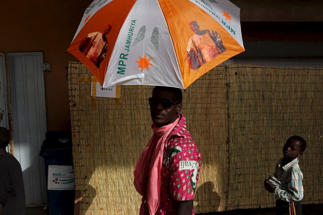 A supporter of incumbent President Mahamadou Issoufou holds an umbrella at a campaign rally in Niamey, Niger, February 18, 2016. (Photo by Joe Penney/Reuters)