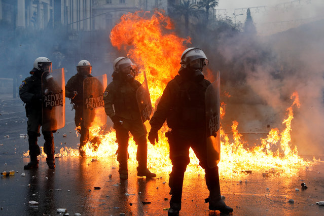Police officers react next to a fire during a demonstration against the agreement reached by Greece and Macedonia to resolve a dispute over the former Yugoslav republic's name, in Athens, Greece, January 20, 2019. (Photo by Alkis Konstantinidis/Reuters)
