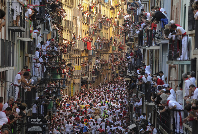 People standing on balconies look at participants as they run in front of Alcurrucen's bulls during the first bull run of the San Fermin Festival, on July 7, 2013, in Pamplona, northern Spain. (Photo by Pedro Armestre/AFP Photo)