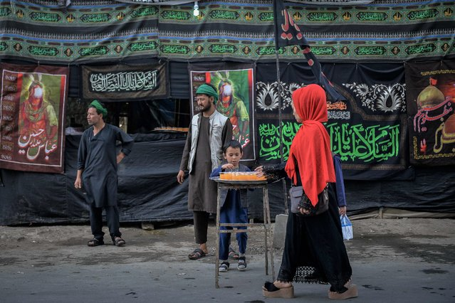 Shiite Muslims distribute sherbet during the Ashura procession which is held to mark the death of Imam Hussein, the grandson of Prophet Mohammad, along a road in Kabul on August 19, 2021, amid the Taliban's military takeover of Afghanistan. (Photo by Hoshang Hashimi/AFP Photo)