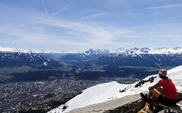 A woman enjoys the view from Seegrube mountain on a sunny spring day in Innsbruck April 15, 2015. (Photo by Dominic Ebenbichler/Reuters)