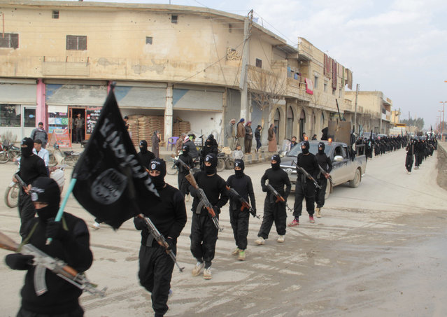 Fighters of al-Qaeda linked Islamic State of Iraq and the Levant carry their weapons during a parade at the Syrian town of Tel Abyad, near the border with Turkey January 2, 2014. Picture taken January 2, 2014. (Photo by Yaser Al-Khodor/Reuters)