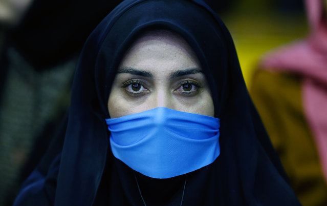 An Iranian supporter of reformist group covers her face with light-blue scarf (the colure of the reformists for the parliament elections) during the first reformists election campaign in Tehran, Iran, February 18, 2016. (Photo by Abedin Taherkenareh/EPA)