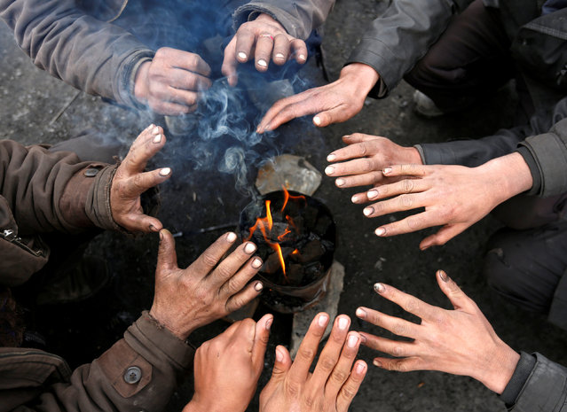 Labourers working at a coal dump site warm themselves by a fire during a cold day on outskirts of Kabul, Afghanistan January 17, 2017. (Photo by Mohammad Ismail/Reuters)