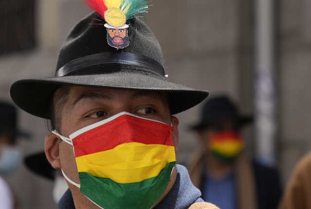 A performer wears a mask with a Bolivian flag motif, due to the COVID-19 pandemic, as he dances  on the National Day of the Morenada Dance in La Paz, Bolivia, Tuesday, September 7, 2021. La Morenada is a folk dance from the Andes that was inspired by slaves brought to the region during the colonial era. (Photo by Juan Karita/AP Photo)