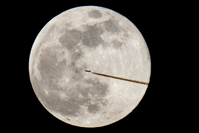 A plane flies past a full moon, Tuesday, February 19, 2019, in Nuremberg, Germany. Tuesday's full moon, or supermoon, appears brighter and bigger than other full moons because it is close to its perigee, which is the closest point in its orbit to Earth. (Photo by Daniel Karmann /dpa via AP Photo)