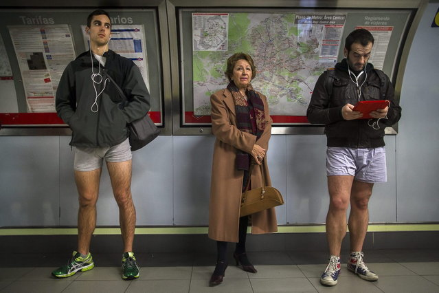 """A passenger stands in between participants as they wait for the train without their pants during the 5th annual """"No Pants Subway Ride"""" in Madrid, Spain, Sunday, January 12, 2014. (Photo by Andres Kudacki/AP Photo)"""
