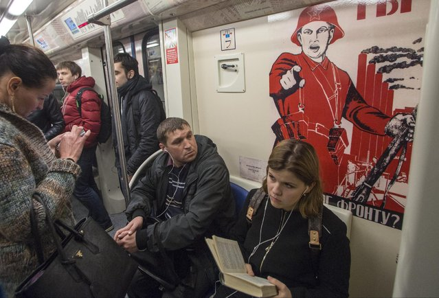 "Passengers ride a subway train decorated with World War II era posters during its first trip in Moscow, Russia, Wednesday, April 22, 2015. Russia will celebrate the 70th anniversary of the Victory in WWII on May 9, 2015. The poster at right reads, ""What have you done for the front!"". (Photo by Denis Tyrin/AP Photo)"
