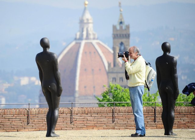 "A man takes photos of sculptures that are part of the exhibition ""Human"" by British artist Antony Gormley at Forte di Belvedere in Florence, Italy, 24 April 2015. More than 100 scultures will be on display from 26 April to 27 September. (Photo by Maurizio Degl'innocenti/EPA)"