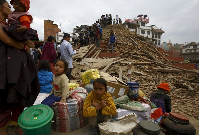 People sit with their belongings outside a damaged temple in Bashantapur Durbar Square after a major earthquake hit Kathmandu, Nepal April 25, 2015. (Photo by Navesh Chitrakar/Reuters)
