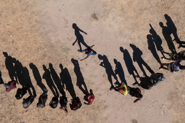 In this aerial view Haitian migrants queue to receive food at a shelter in Ciudad Acuna, Coahuila State, Mexico, on September 23, 2021. At least 50 police vehicles carrying more than a hundred agents are blocking the border crossing at the river that separates the Mexican city of Ciudad Acuña from the United States, AFP reported. (Photo by Pedro Pardo/AFP Photo)