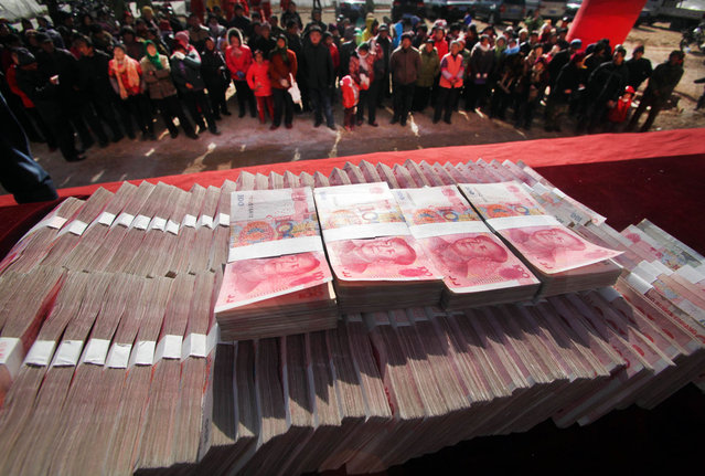 This picture taken on January 20, 2014 shows villagers gathering to receive their share of one million yuan (USD165,000) paid out in year-end bonuses by a tea company at their village in the suburb of Jinan, east China's Shandong province. The biggest payout amounts to 200,000 yuan as the villagers have been growing tea since 2003. (Photo by AFP Photo)