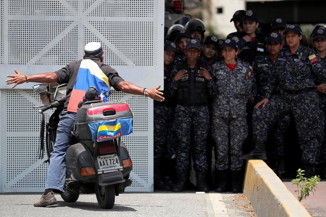 A man on a motorbike gestures against police forces during a rally in Caracas, Venezuela on March 9, 2019. (Photo by Ivan Alvarado/Reuters)