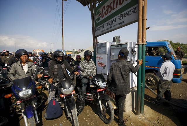 People queue with their motorcycles in front of a petrol pump to fill their gas tanks, following Saturday's earthquake in Bhaktapur, Nepal April 27, 2015. (Photo by Navesh Chitrakar/Reuters)