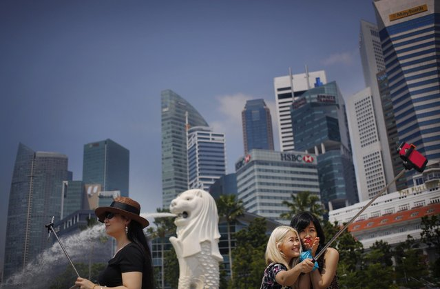 In this April 21, 2015 file photo, tourists use selfie sticks to take photos of themselves with their smartphones, at one of Singapore's popular tourists spots with the financial skyline in the background, in Singapore. (Photo by Wong Maye-E/AP Photo)