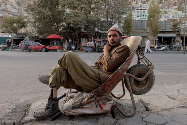A worker with a with a prosthetic leg sits in a wheelbarrow in Kabul, Afghanistan, October 4, 2021.. (Photo by Jorge Silva/Reuters)