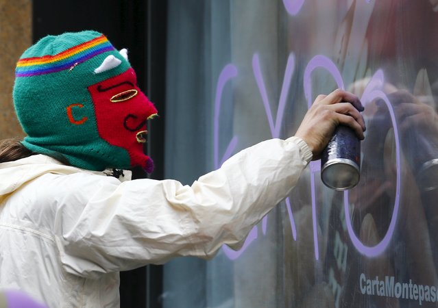 A protester sprays paint on the window of a bank during a rally against Expo 2015 in Milan, Italy, April 30, 2015. The Milan Expo will open in the city on May 1. Officials are counting on some 20 million visitors to the six month-long exhibition of products and technologies from around the world. (Photo by Stefano Rellandini/Reuters)