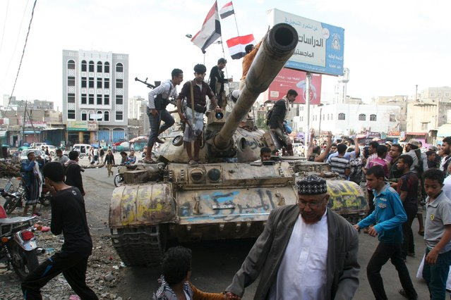 People gather around a tank used by pro-government fighters, after they took the Bir Basha neighborhood from Houthi fighters in Yemen's southwestern city of Taiz March 11, 2016. (Photo by Anees Mahyoub/Reuters)