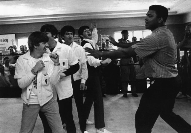 Muhammad Ali, who'll fight heavyweight champ Sonny Liston on February 25, clowns a bit with the Beatles at his training camp in Miami Beach, Florida on Tuesday, February 18, 1964. The Beatles are, from left: Ringo Starr, John Lennon, George Harrison, and Paul McCartney. (Photo by AP Photo)