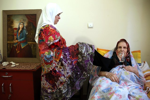 In this picture taken on Thursday, January 28, 2015, Zohreh Etezadossaltaneh uses her foot to help her mother to drink water at their home, in Tehran, Iran. (Photo by Ebrahim Noroozi/AP Photo)