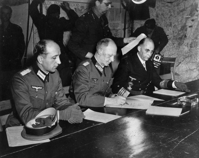 In this May 7, 1945 file photo, Gen. Alfred Jodl, center, signs the unconditional surrender of all armed German forces imposed by the Allied Powers, at Supreme Commander Eisenhowers headquarters in Rheims, France. He is flanked by Gen. Wilhelm Oxenius, Commander of the German Luftwaffe. (Photo by AP Photo)