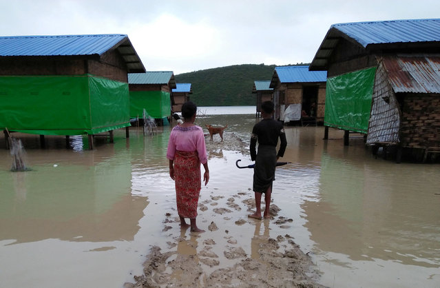 Muslim residents at Taungpaw an internally displaced people's camp walk through the flood to reach the new house built by the Myanmar government in central Rakhine, Myanmar, June 14, 2018. (Photo by Reuters/Stringer)