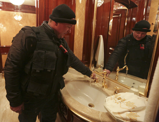 A man turns on a water tap inside the residence as anti-government protesters and journalists walk on the grounds of the Mezhyhirya residence of Ukraine's President Viktor Yanukovich in the village Novi Petrivtsi outside Kiev February 22, 2014. (Photo by Konstantin Chernichkin/Reuters)
