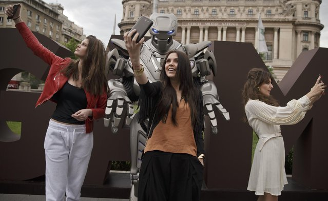 """People take """"selfies"""" with Titan the Robot, in Bucharest, Romania, Monday, May 11, 2015. Titan the robot is produced by British company Cyberstein Robots Ltd and gained world recognition in pop videos dancing alongside artists such as Rihanna in music videos. (Photo by Vadim Ghirda/AP Photo)"""