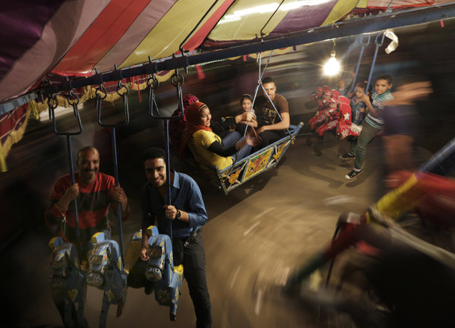 In this photo taken Tuesday, May 12, 2015, people ride on a carousel as they celebrate a religious festival, or moulid, which commemorates of the birth of Muslim Prophet Muhammad's granddaughter Sayyeda Zeinab, outside the mosque and shrine named for her, in Cairo, Egypt. (Photo by Amr Nabil/AP Photo)