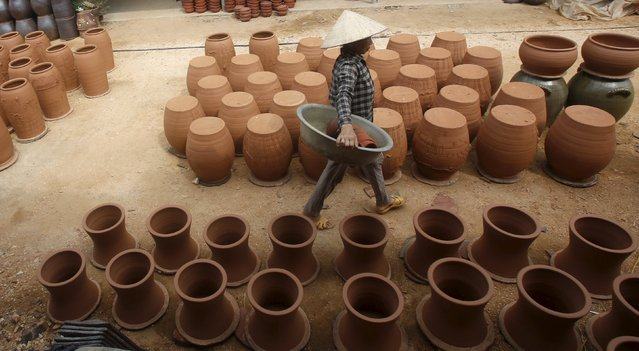 A woman puts clay products to dry at a factory at Phu Lang pottery village in Bac Ninh province, Vietnam, May 14, 2015. (Photo by Reuters/Kham)