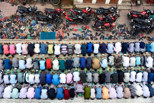 Indian Muslims offer last congregational Friday prayers of the holy month of Ramadan on a road in Agartala on May 31, 2019. Muslims around the world took part in the Friday prayers ahead of the Eid al-Fitr festival marking the end of the fasting month of Ramadan, which depends on the sighting of the moon. (Photo by AFP Photo/Stringer)