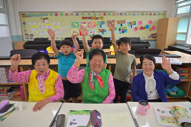 This picture taken on May 15, 2019 shows elderly South Korean women (front L-R) Park Young-ae, Nam Yang-soon and Shin Dong-hee posing and their eight-year-old classmates in a classroom at Woldeung Elementary School on the outskirts of Suncheon, 320 kilometres (198 miles) south of Seoul. With South Korea's population ageing rapidly and families migrating from the countryside to the cities for decades, rural primary schools are facing falling pupil numbers. Now some are targeting the opposite end of the age spectrum and recruiting elderly illiterate grandmothers – who were denied education on gender grounds during their own childhoods – to stave off the threat of closure and teach them to stave off the threat of closure and teach them to read and write. (Photo by Jung Yeon-Je/AFP Photo)