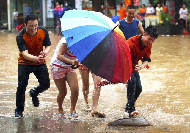 People catch a fish on a flooded street after heavy rainfall in Dongguan, Guangzhou province, China, May 20, 2015. (Photo by Reuters/China Daily)