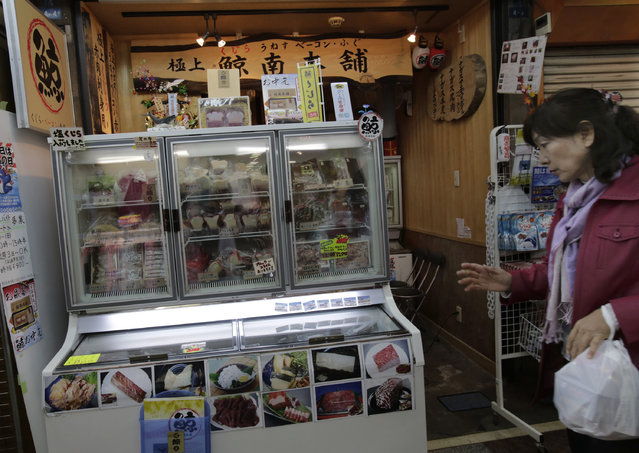 In this March 27, 2014 file photo,a shopper walks past a whale meat specialty store at Tokyo's Ameyoko shopping district. The International Court of Justice on Monday, March 31, 2014, ordered a temporary halt to Japan's Antarctic whaling program, ruling that it is not for scientific purposes as the Japanese had claimed. Australia had sued Japan at the U.N.'s highest court for resolving disputes between nations in hopes of ending whaling in the icy Southern Ocean. (Photo by Shizuo Kambayashi/AP Photo)