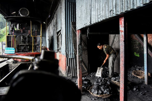 A worker breaks coal for a steam engine belonging to Darjeeling Himalayan Railway, which run on a 2 foot gauge railway and is a UNESCO World Heritage Site, at a station in Darjeeling, India, June 25, 2019. (Photo by Ranita Roy/Reuters)