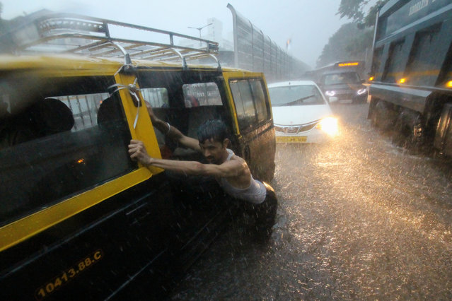A man pushes a taxi through a waterlogged street during heavy rains in Mumbai, India on 01 July 2019. Monsoon in India officially lasts from June to September. (Photo by Himanshu Bhatt/NurPhoto via Getty Images)