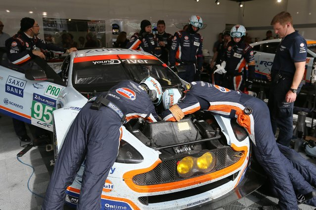 Mechanics repair the Aston martin Vantage V8 No95 of the Aston Martin Racing team driven by Danish drivers Marco Sorensen, Nicki Thiim and Christoffer Nygaard during the 83rd 24-hour Le Mans endurance race, in Le Mans, western France, Saturday, June 13, 2015. (AP Photo/David Vincent)