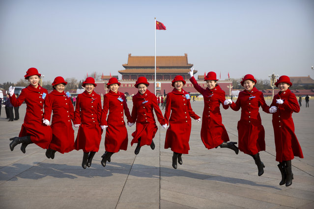 Bus ushers leap as they pose for a group photo at Tiananmen Square during a plenary session of the National People's Congress in Beijing, Saturday, March 4, 2017. China will raise its defense budget by about 7 percent this year, a government spokeswoman said Saturday, continuing a trend of lowered growth amid a slowing economy. (Photo by Mark Schiefelbein/AP Photo)