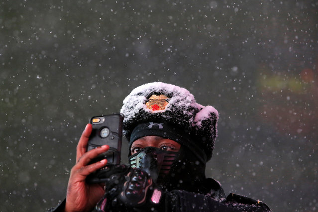 Times Square Public Safety Sergeant Baldwin Davis captures falling snow with his cellular device in Times Square in Manhattan, New York, U.S., March 14, 2017. (Photo by Andrew Kelly/Reuters)