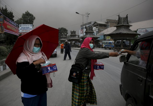 Women give out face masks to people as ash from Mounth Sinabung volcano falls on the town of Brastagi, North Sumatra province, Indonesia, June 25, 2015. (Photo by Reuters/Beawiharta)
