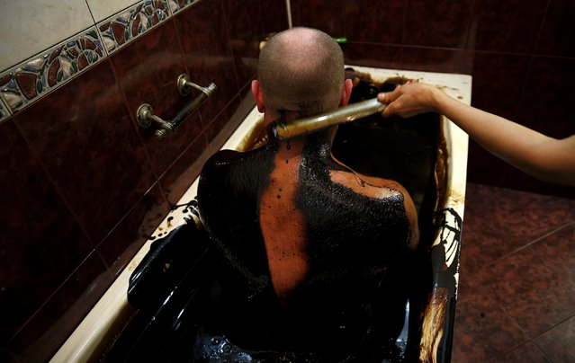 A man gets his back cleaned of crude oil as he lies in a bathtub during a health therapy session at Naftalan Health Center in Baku, Azerbaijan June 27, 2015. According to Hashim Hashimov, a medical specialist at the centre, the oil can heal more than seventy diseases, including neurological diseases, skin conditions and impotence. Centres like Naftalan attract people coming from Russia, Kazakhstan and Germany, Hashimov told Reuters. (Photo by Stoyan Nenov/Reuters)