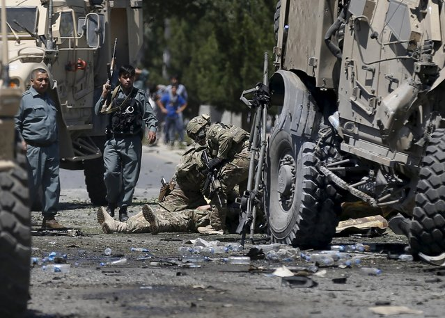 U.S. soldiers attend to a wounded soldier at the site of a blast in Kabul, Afghanistan June 30, 2015. A suicide bomber attacked a convoy of foreign troops serving with NATO on the main road running between Kabul's airport and the U.S. embassy, police and security officials said. (Photo by Mohammad Ismail/Reuters)