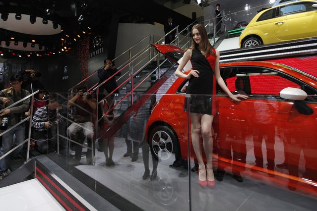 """A model (C) poses by a Fiat car on display at the China International Exhibition Center new venue during the """"Auto China 2014"""" Beijing International Automotive Exhibition in Beijing on April 20, 2014. (Photo by AFP Photo)"""