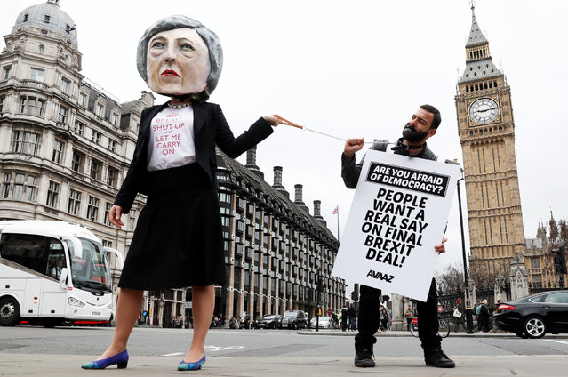 Anti-Brexit protesters, one wearing a giant Theresa May head, hold placards outside Parliament on the day the Prime Minister will announce that she has triggered the process by which Britain will leave the European Union, in London, March 29, 2017. (Photo by Stefan Wermuth/Reuters)