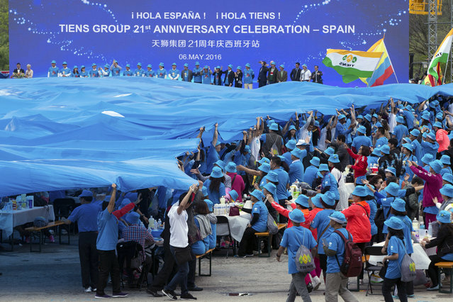 Chinese conglomerate Tiens Group employees unfurl a giant banner during a celebration in Madrid, Spain, Friday, May 6, 2016. (Photo by Paul White/AP Photo)