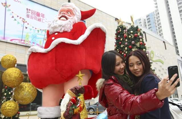Women take pictures in front of a Santa Claus figure outside a shopping mall ahead of Christmas in Dongguan, Guangdong province, December 20, 2012. (Photo by Reuters/China Daily)