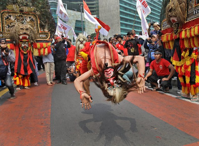 A masked dancer somersaults as he performs during a May Day rally in Jakarta, Indonesia, Thursday, May 1, 2014. (Photo by Dita Alangkara/AP Photo)